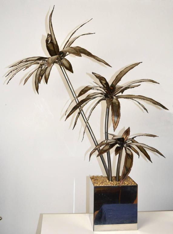 An exceptional pair of large steel palm tree sculptures in the manner of Maison Jansen. Three metal trunks with patinated fronds in a polished steel planter with fixed gravel 'mulch.'
