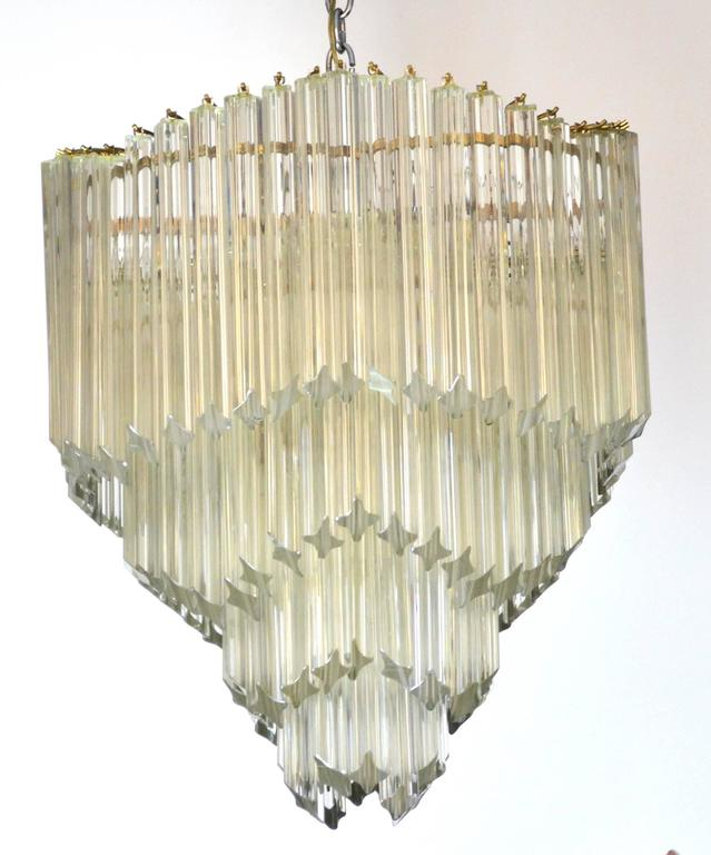 A Mid-Century Modern chandelier with four tiers of Venini Murano crystal triedre prisms. Each undulating tier of crystals catches and amplifies light from five Edison base sockets.