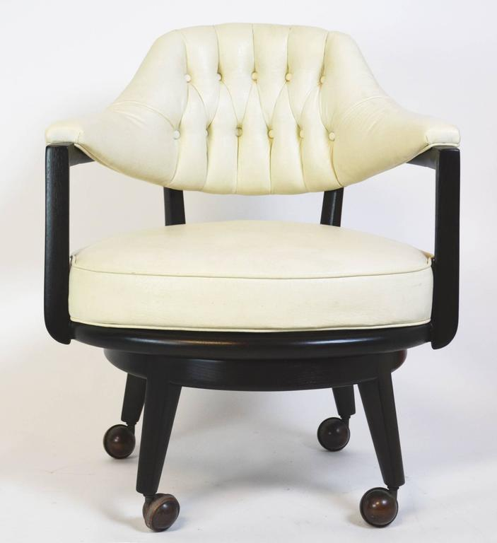 A fantastic pair of Monteverdi-Young swivel chairs designed by Maurice Bailey. Refinished, ebonized wood frame and base with original castors. Original upholstery and button tufted white leatherette in good condition, with age appropriate wear and