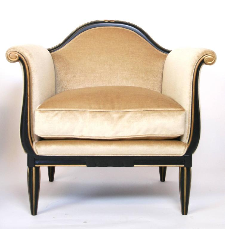 A pair of French Art Deco lounge chairs in the manner of Paul Follot. Black lacquered and gold carved, fluted legs and frame. Newly upholstered.