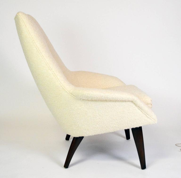 "A sculptural Danish lounge chair with a loose seat cushion and tufted back, on curved, tapered walnut legs. Arm height 20"" at front,