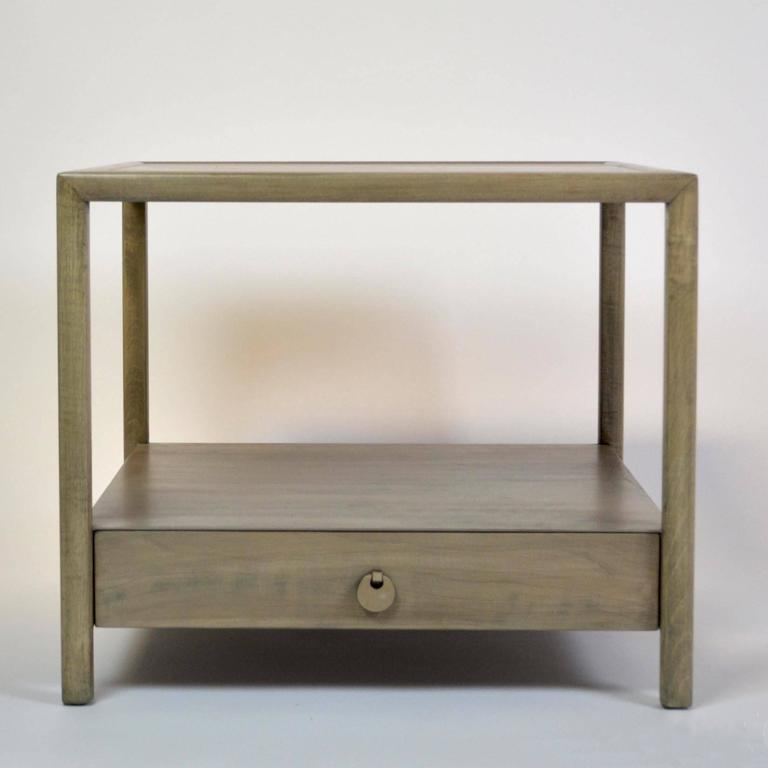 An end table or nightstand by Michael Taylor for Baker Furniture's New World collection. refinished in a pale grey stain.
