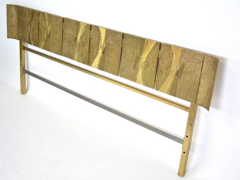 A bronze headboard by Luciano Frigerio, Italian, circa 1960, composed of six cast bronze panels flanked by curved panels on each end.