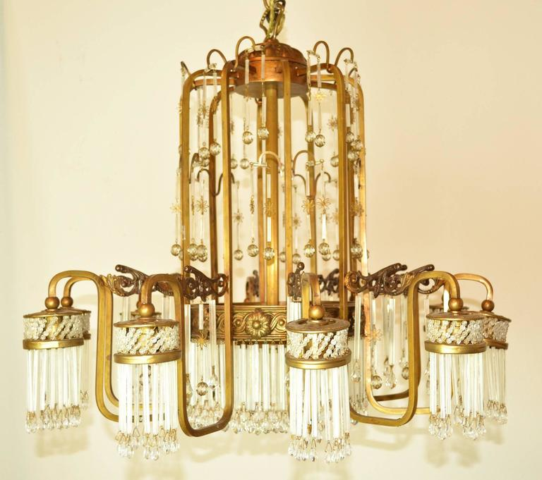 An Art Deco chandelier with a gold tone metal frame with cascading glass rods and beads. Ten lights, each surrounded by glass rods.