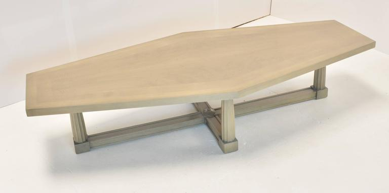 A Baker coffee table, circa 1960, with a elongated diamond like top on four Doric column legs on a cross stretcher. Top is inlaid with figured and flamed bleached mahogany, in a grey/silver finish.