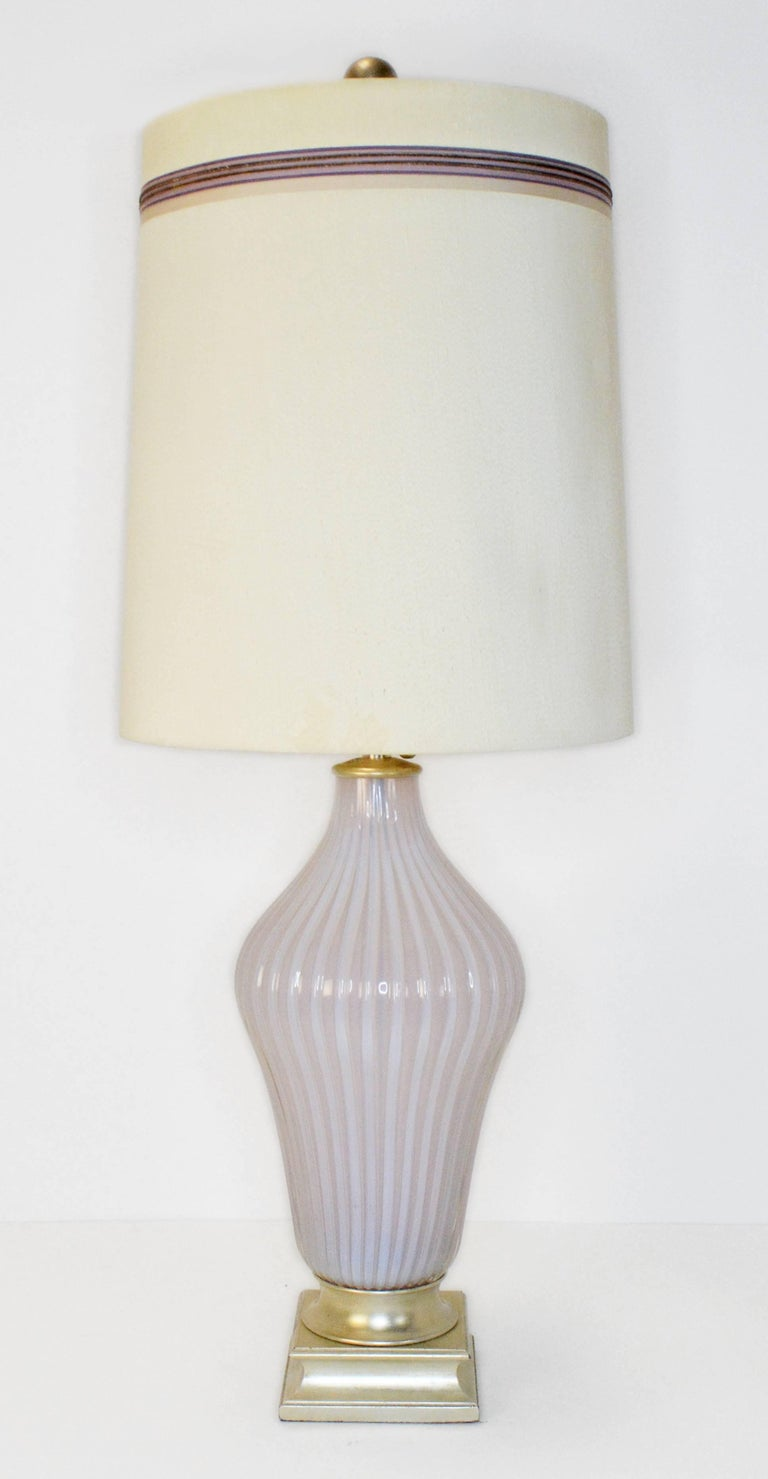 A rare pair of vintage Murano table lamps by Seguso for Marbro. Ribbed Murano opaline glass lamps in a light blush pink retailed by The Marbro Lamp Company on original silver leafed bases. The soft glow of the opaline glass is amazing. Lamps have