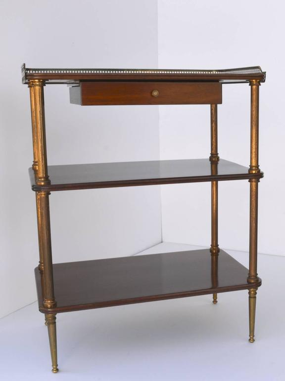 A fine pair of Mid-Century French neoclassical side tables, with three mahogany shelves supported on fluted brass columns with decorative capitals, resting on tapered brass legs. The top has a three sided pierced brass gallery and a small drawer
