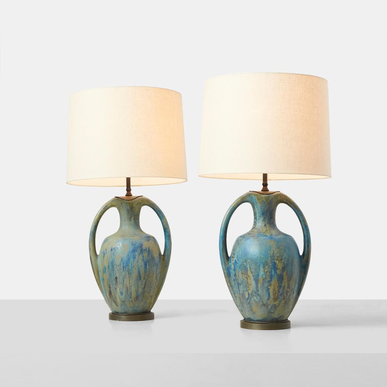 Pair of Danish Amphora shaped pottery lamps. An elegant pair of pottery lamps with an amphora shape on metal stands. Beautiful glaze in shades of blue, green, and ochre. Rewired with braided cloth cord. Denmark, circa 1950s.