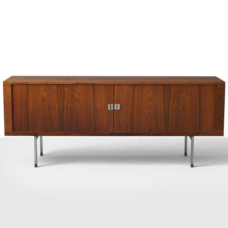 A low sideboard by H. J. Wegner. Features a Brazilian rosewood front with two tambour doors enclosing oak shelves and sliding trays. Chromed metal base with rosewood leg ends. Produced by Ry Møbler. Includes certificate from the Danish forest and