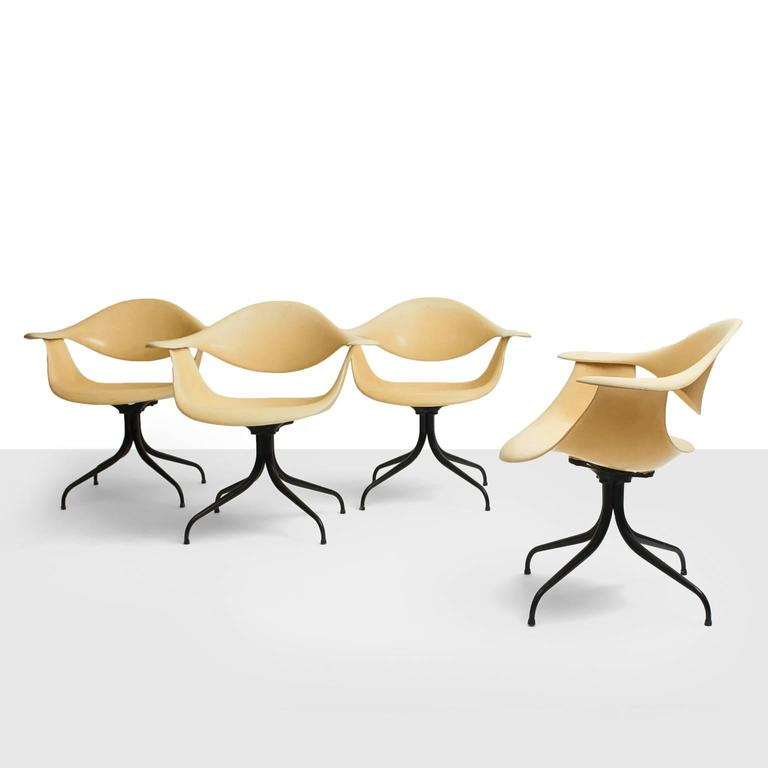 A rare set of four swag legged dining chairs designed in 1958 by George Nelson for Herman Miller. Cream colored fiberglass on a black enameled base. All in excellent original condition. First editions from 1958.
