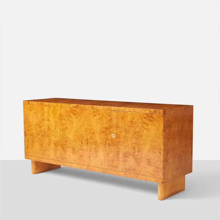 A rare root wood veneered sideboard designed in 1935 by Architect Axel Einar Hjorth. Cabinet has three doors with adjustable shelves on two right sections and the left side having three felt lined pull out drawers. The cabinet retains the original