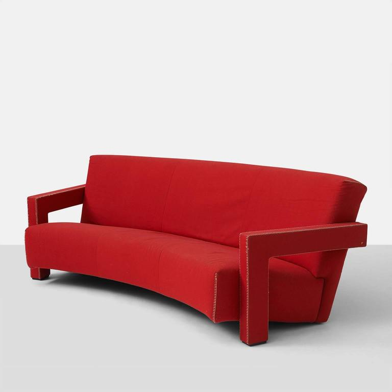 A very early edition of Gerrit Rietveld's Utrecht sofa designed in 1935 and made by Cassina in the late 1960s. This curved back sofa retains the original red wool flannel fabric with ivory hemstitch trim. Original label and signature are intact.