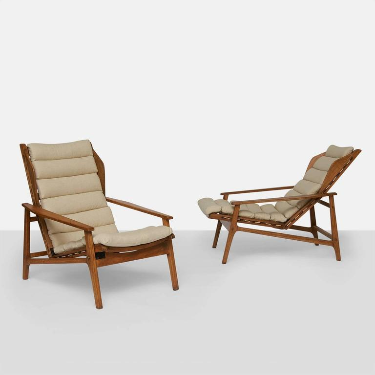 A very rare pair of armchairs in oak by Gio Ponti retaining the original Cassina label. The chairs are a variation on model #811 and were designed in 1957. Each can be adjusted to five different reclining positions. The linen cushions are held onto