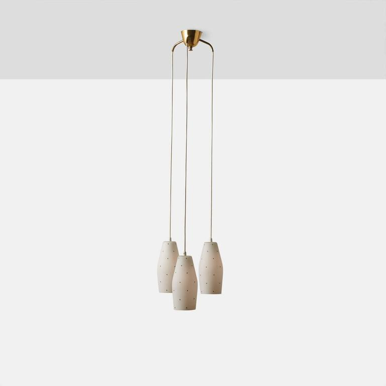 A cascading chandelier by Lisa Johansson-Pape with three white glass shades hand painted with black dots. The canopy is brass each shade has a new US size porcelain socket. Chandelier was made in Finland in the 1960s.