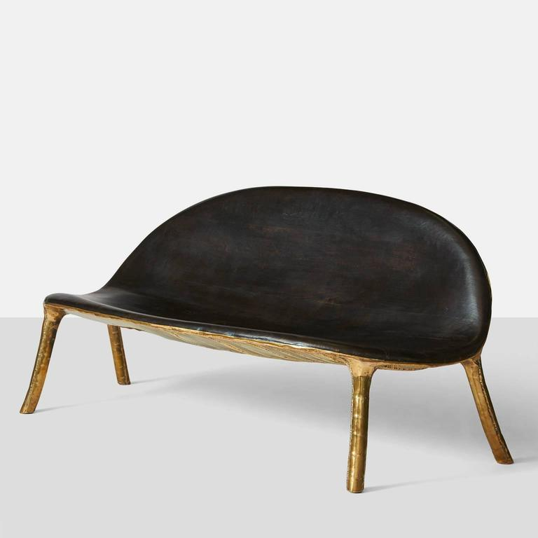 A sofa by German furniture designer Valentine Loellmann made in 2015. Completely hand constructed in brass and not cast, with a charred oak seat and back that has been made to fit the curved shape. The brass construction creates a unique pattern on