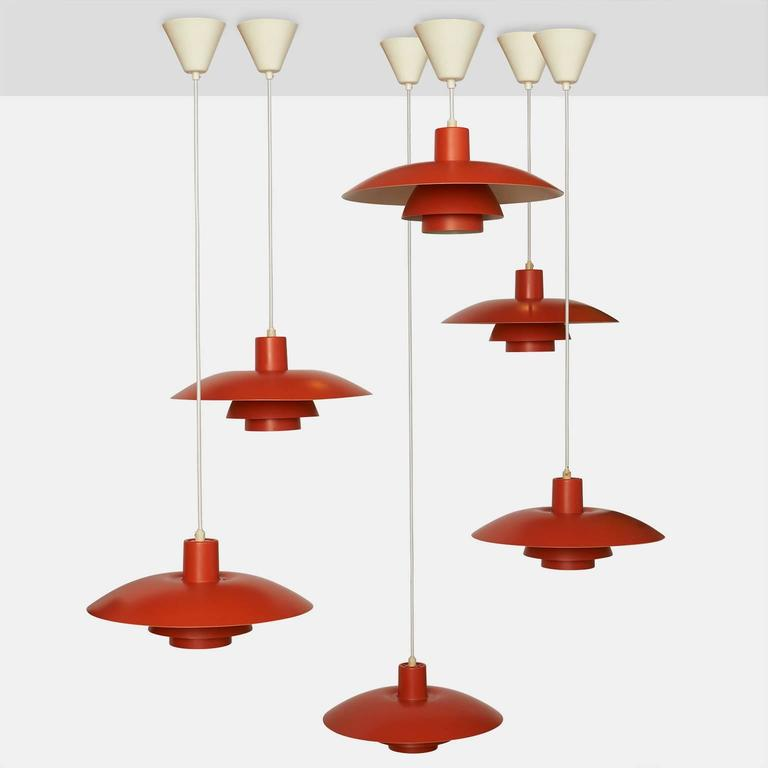 A group of eight orange lacquered metal pendants by Poul Henningsen for Louis Poulsen, Denmark. Each pendant has 8' of cord.