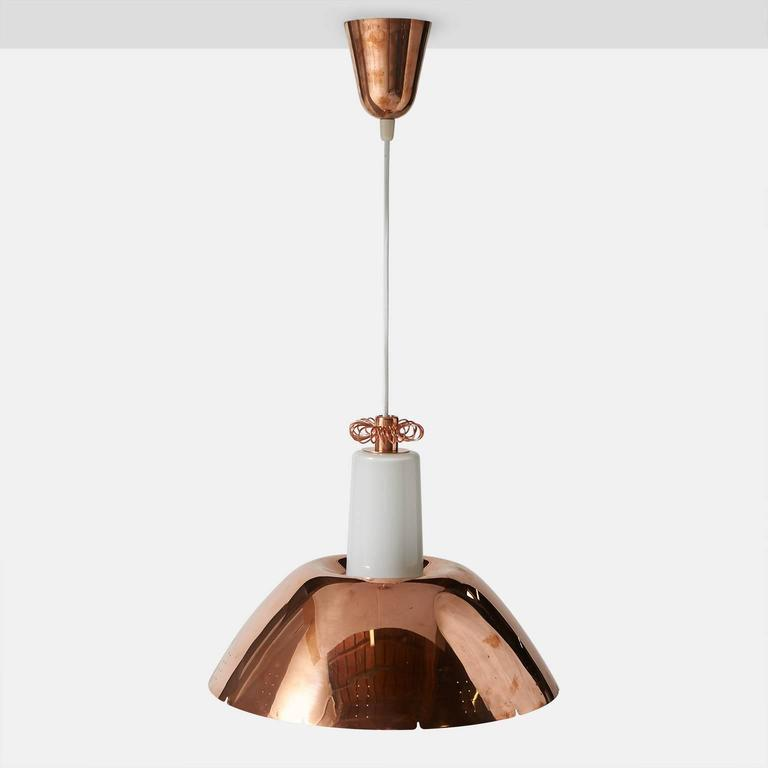 A pendant by Paavo Tynell with a perforated copper shade over a white glass diffuser with one Edison base socket. The top of the pendant features a copper spiral rosette. Model #K2-20 for Idman Oy, circa 1950s, Finland.