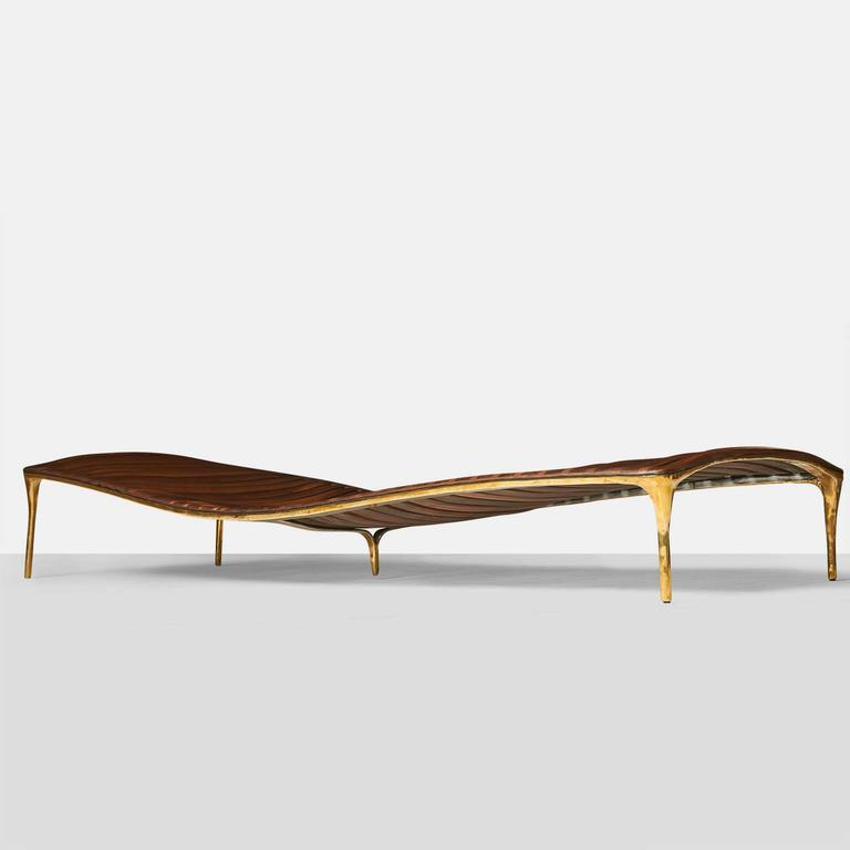 A large-scaled daybed in hand-worked brass with walnut cross beam support. Shaped to support a reclining body, the daybed has an overall organic shape. Each piece is completely handmade by Valentin Loellmann and all are signed and numbered. Valentin