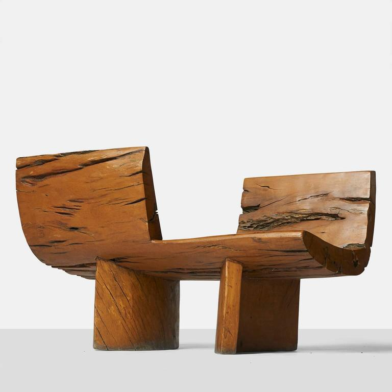 A tete a tete by Hugo Franca made of naturally fallen Brazilian hardwood trees. The design is made of opposing seats on two semi circular bases,