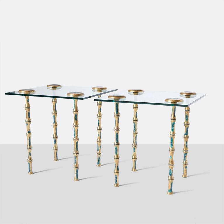 A pair of side or coffee tables with glass top and decorated solid brass legs.  The four legs attach thru the glass top with a brass star shaped cap. Mexico, c. 1950's