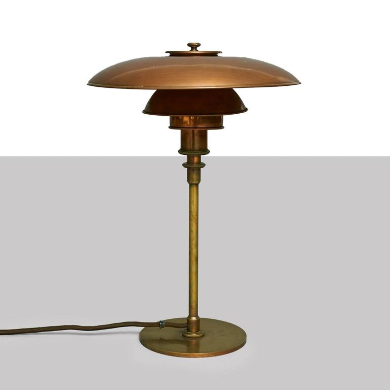 A table lamp by Poul Henningsen with browned brass frame, socket cover and top, mounted with 3/2 patinated copper shade set. No switch on the frame. Stamped 'Pat. Appl.' (highly valued to PH collectors). Early model produced by Louis Poulsen in