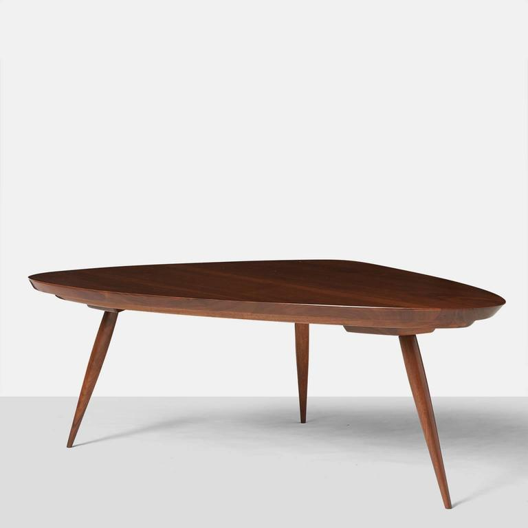 An extra large triangular shaped coffee table with rounded corners in black walnut on tapered legs. A pair of smaller version tables are available,