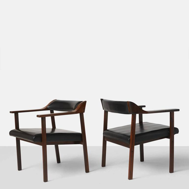 A pair of chairs in Jacaranda and upholstered in black faux leather, made in Brazil, circa 1950 by Joaquim Tenreiro. A total of four chairs are available.