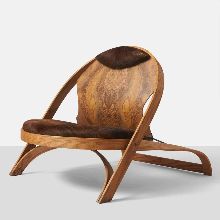 A limited edition chair by Richard Artschwager in oak with cowhide seat and headrest and a painted steel support on the backside. Richard Artschwager, 1923-2013, is a renowned artist with shows from the Whitney Museum in New York to the Centre