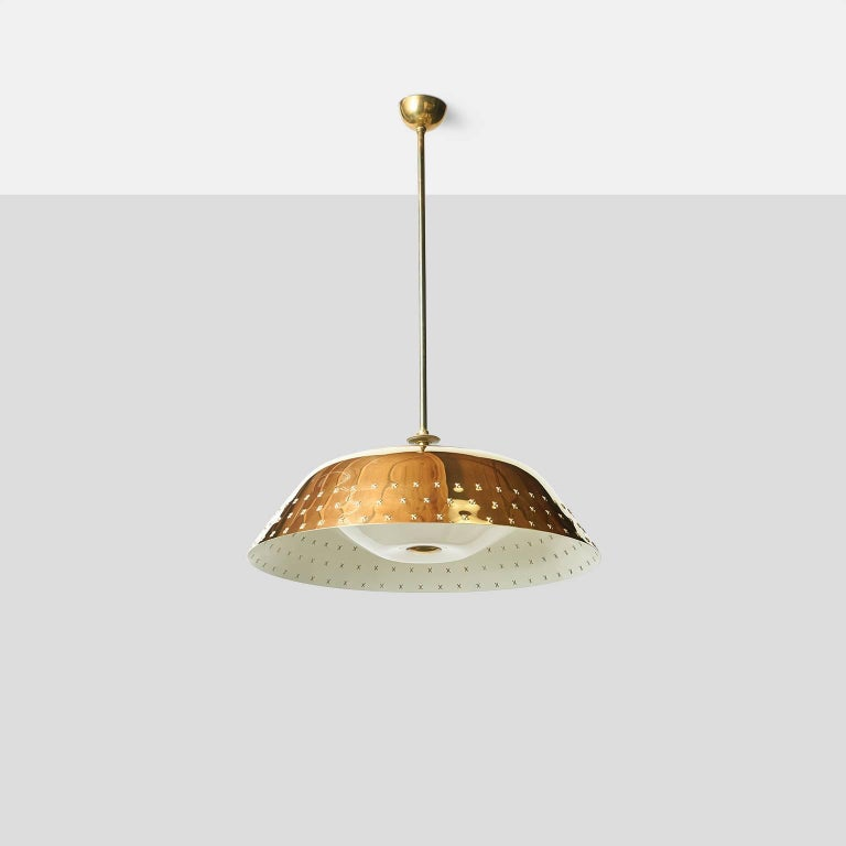 A brass chandelier with perforated X-pattern detail around perimeter, translucent dome covers the bulbs with a brass finial in the center. Manufactured by Orno. 