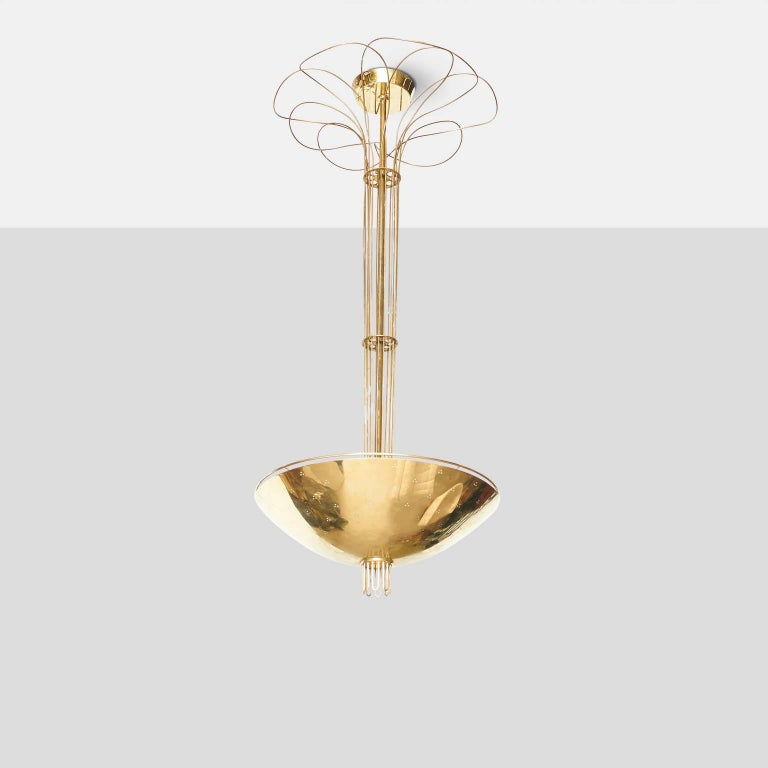 An extremely rare large-scale chandelier by Paavo Tynell. The chandelier features a brass floral detail at the top, cascading brass detail along the stem with a perforated brass shade, raised gallery edge, and a fluted brass detail on bottom center.
