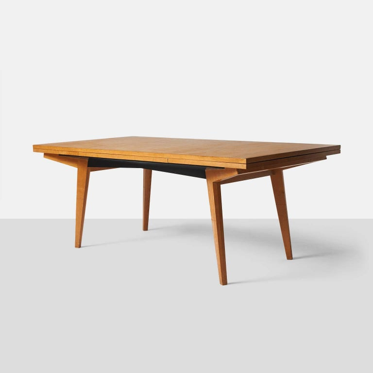 A dining table by Maxime Old in French oak with two leaves underneath that extend on each end to create a 120