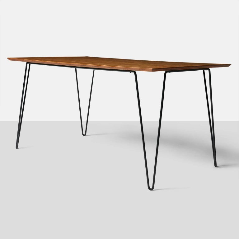 Dining table by Dorothy Schindele. A rectangular dining table with a pale walnut top, eased edge, and resting on black enameled hair pin legs. USA, circa 1950s.