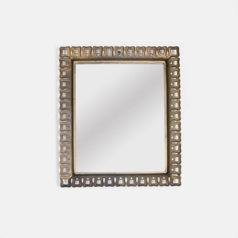 A tailored mirror with a unique cast brass edge detail by Paolo Buffa.