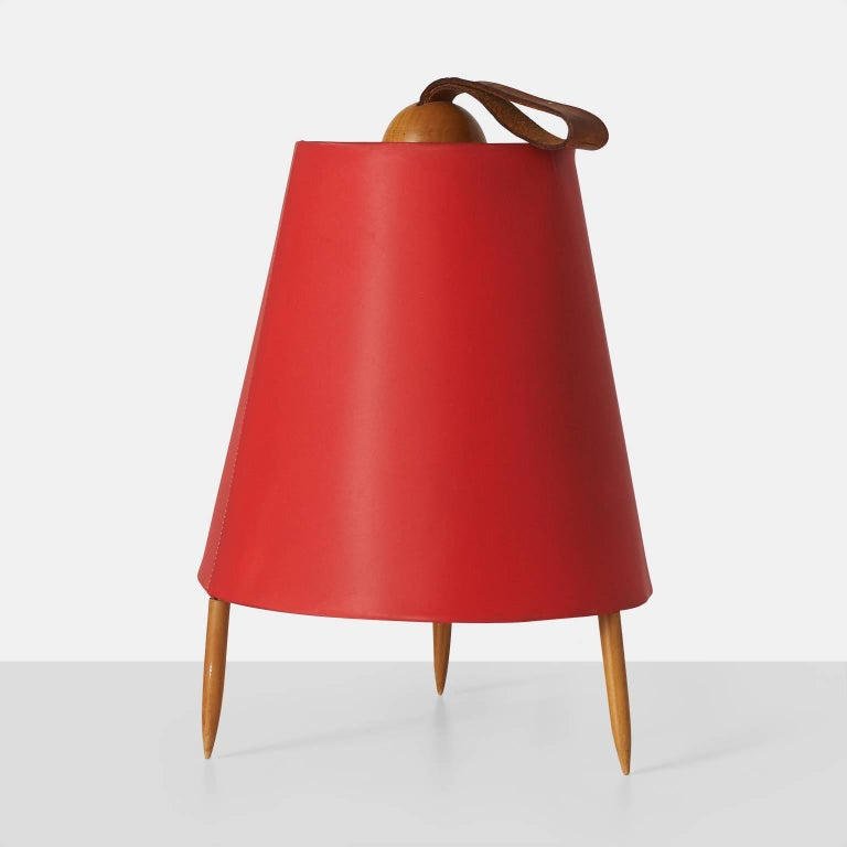 """A desk or table lamp known as Eichhornchen or """"squirrel"""" lamp in red lacquered linen with three teak legs and a leather loop at the top. Made by J.T.Kalmar. Austria, circa 1950s."""