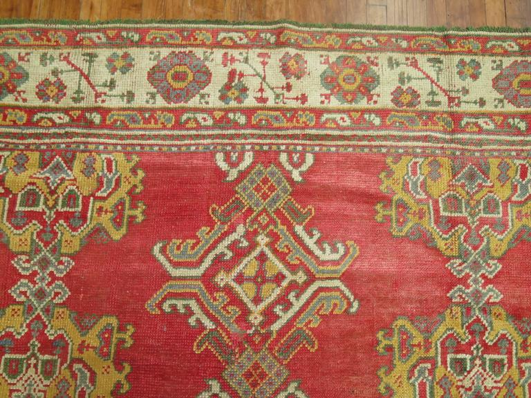 A colorful Oushak carpet with a Classic all-over crab/lobster motif. The colors on this piece is what most attracted us to add it to our collection. Pinkish red field, accents in mustard, green, gray and ivory highlight this piece which is in
