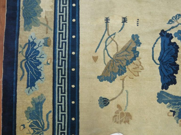 An early 20th century exquisite Chinese Peking rug with an enchanting design and multi-band border in predominant shades of ivory and blue.