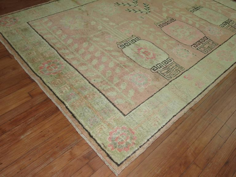 One of a kind Khotan rug with a soft pink field consisting of a flower vase motif and a soft green border.