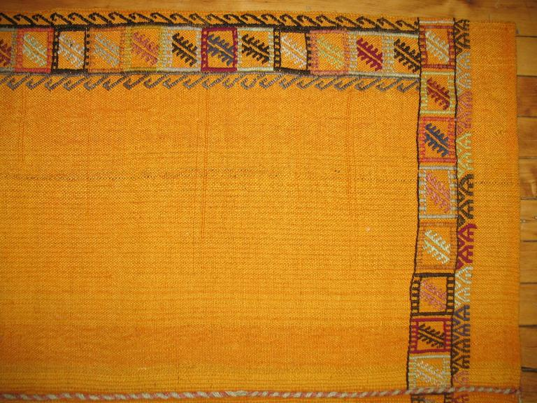Throw square size flat-weave with a plain solid design in goldish yellow surrounded by a tribal border.