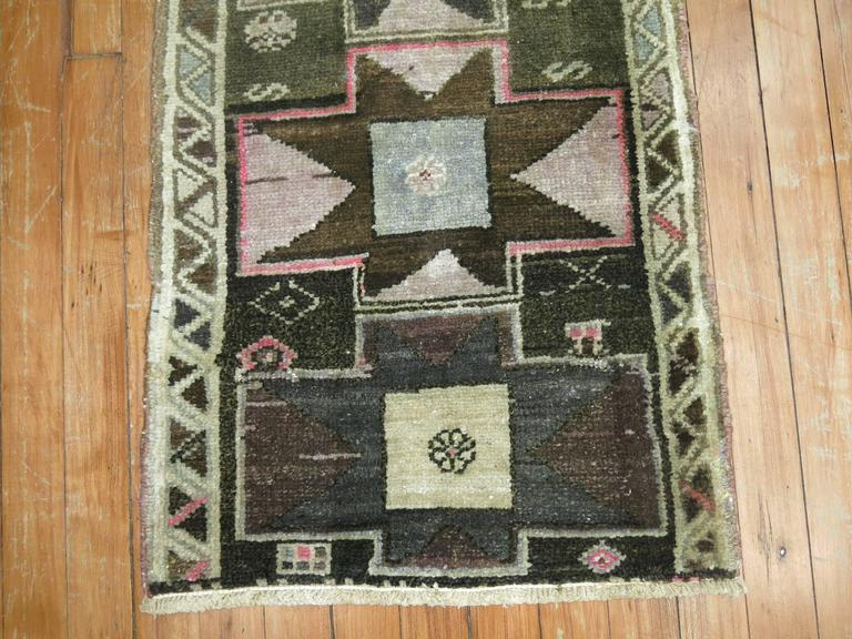 A vintage Turkish Anatolian mat in deep browns and gray with pink accents.