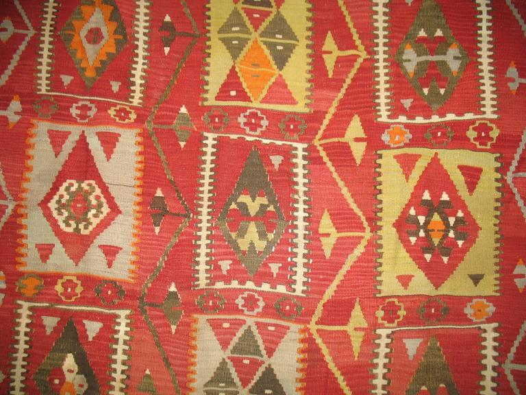 Vintage Turkish Kilim with a colorful repetitive square design on a dark red colored ground.
