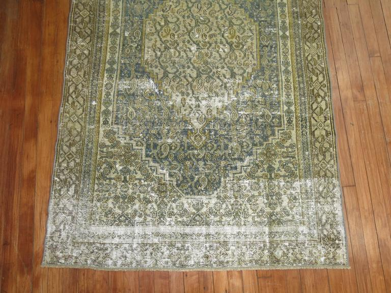 A perfectly worn Persian geometric Bibikabad rug in green, gray and gold.