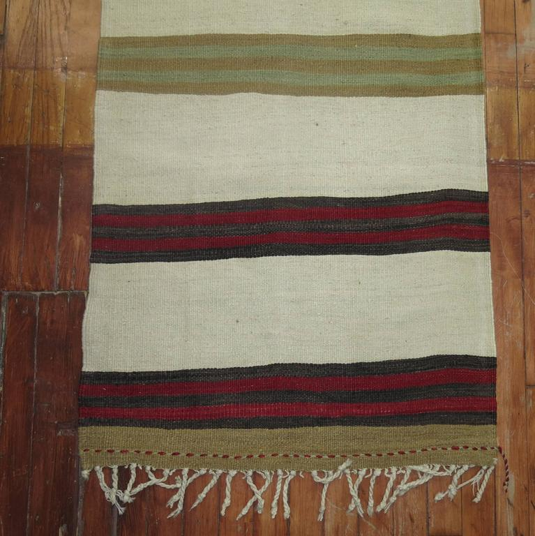 A mid-20th century narrow and long Turkish Kilim runner featuring an ivory colored ground,