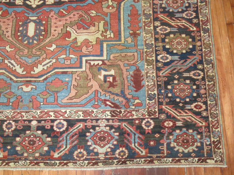 A room size antique Persian Heriz rug featuring accents of blue.  Originating in Northwest Persia and the Iranian province of East Azerbaijan, Heriz Oriental rugs from Persia include regional patterns created in several different towns and