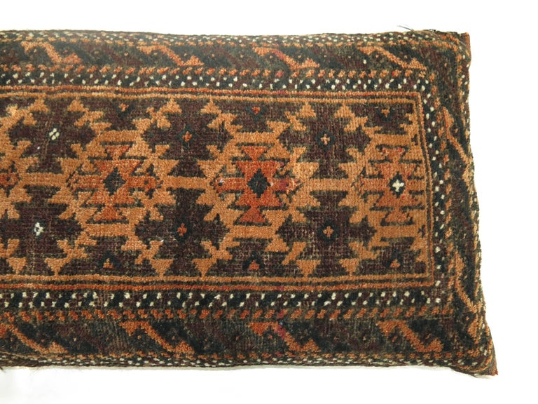 Large pillow made from a 19th century balouch rug with a rusty colored Kilim backing. Sewn shut.