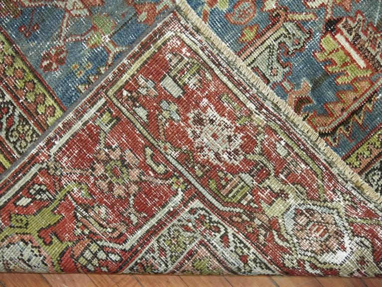 A shabby chic Persian Heriz textured rug.