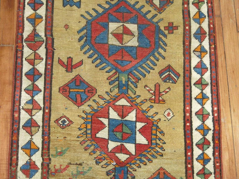 An early 20th century tribal Persian Serab runner with bright colors on a camel colored ground.