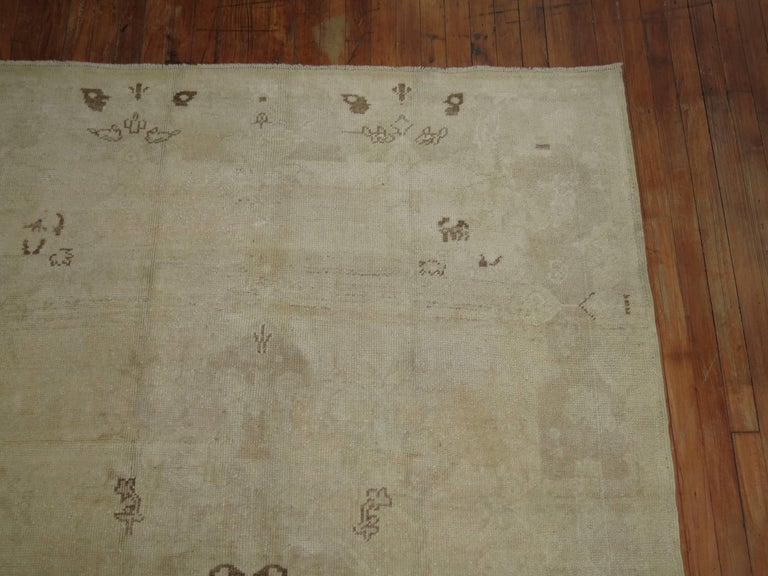 Predominantly white colored vintage Turkish intermediate size Oushak rug.