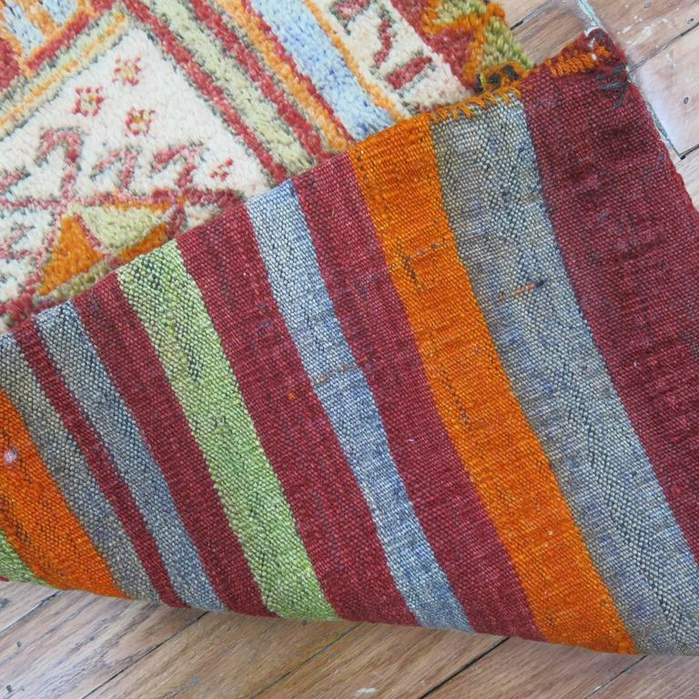 A bright Turkish yastik rug with striped Kilim back intact. One end and two sides are sewn shut while other end was kept open. Can be used as a throw piece or wall covering too.