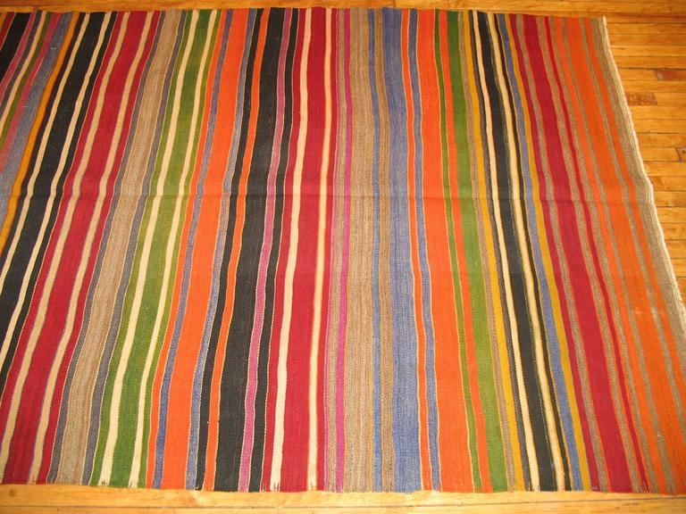 Mid-20th century handmade, one of a kind Turkish Kilim with a brightly colored striped design.