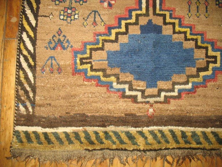 A tribal antique Persian Gabbeh in camel, creams, yellow, browns and rusts.